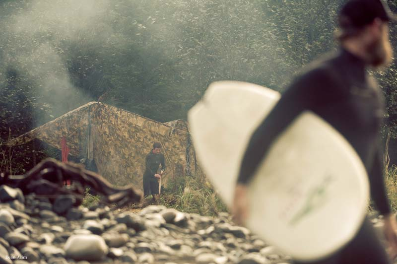 A surfer walks by in the foreground, while a campmate tends to the camping arrangements in the background