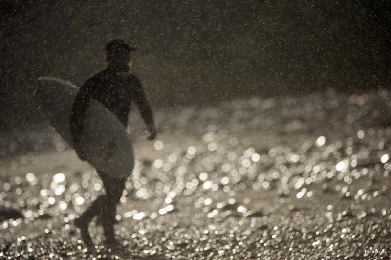 A surfer in a wet suit walk up the beach while the rain pours down on him and his board