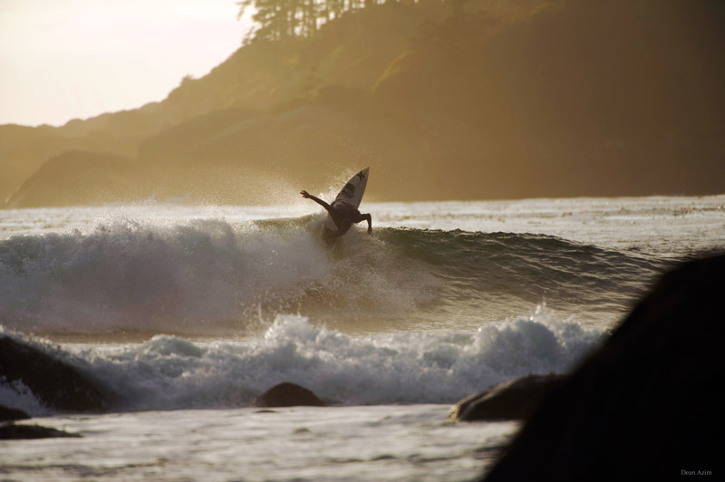 A surfer rips off the lip of wave in the sunset