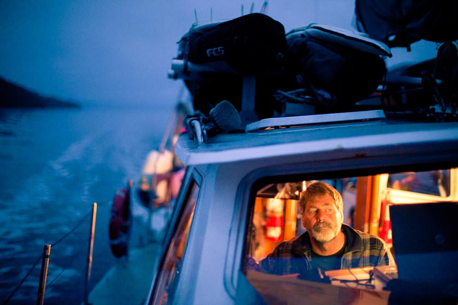 Brian Falconer is down below and lit up by the cabin lights of the sailboat